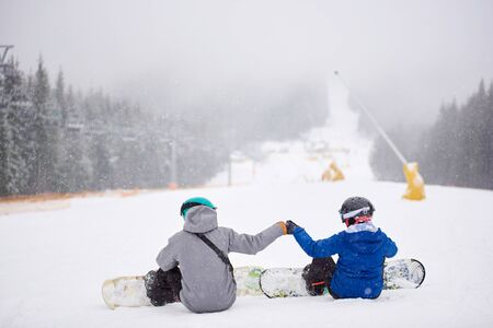 Back view of sportsmen couple sitting on snow before freeriding from ski run at ski resort. Man and woman doing fist bump. Snowfall in mountains. Friendship, support, decision, sport, extreme conceptの写真素材