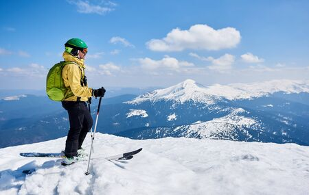 Foto für Sportsman skier in helmet and goggles with backpack standing in profile on skis holding ski poles in deep white snow, on copy space background of bright blue sky enjoying beautiful mountain view. - Lizenzfreies Bild