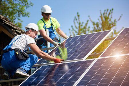 Photo pour Two professional technicians installing heavy solar photo voltaic panels to high steel platform. Exterior solar system installation, alternative renewable green energy generation concept. - image libre de droit
