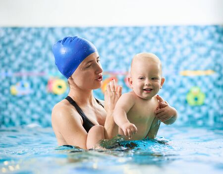 Photo pour Swimming class for infants. Young mother supporting her baby in swimming pool and giving instructions, happy little boy enjoying interaction with his mom. Concept of happy childhood - image libre de droit