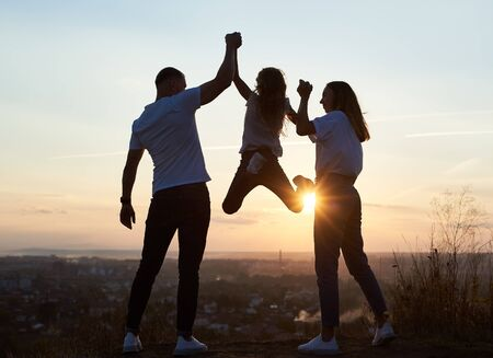 Photo pour Silhouette of father mother and their daughter spending fun day outside the city on the hill on the sunset with a beautiful city view, dad and mom holding girl by hands and she is hanging, back view - image libre de droit