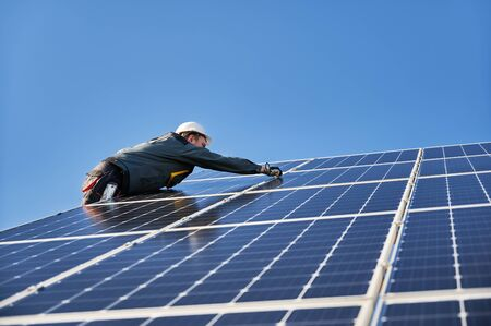 Photo for Male worker mounting solar modules, panels and support structures of photovoltaic solar array. Electrician wearing safety helmet and gloves. Concept of sun energy and power sustainable resources. - Royalty Free Image