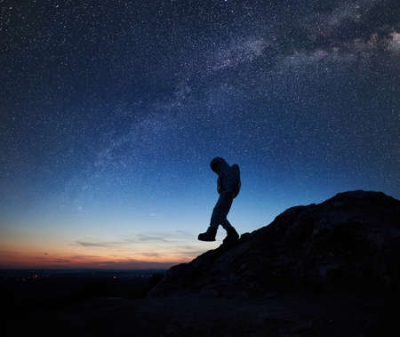 Photo pour Astronaut climbing down the mountain under beautiful night sky with stars and Milky way. Silhouette of cosmonaut in space suit exploring new planet. Concept of space travel, galaxy and human in cosmos - image libre de droit