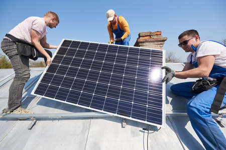 Photo pour Male team workers installing solar photovoltaic panel system. Three electricians lifting blue solar module on roof of modern house. Sustainable resources innovation environmental concept. - image libre de droit