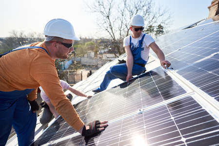 Photo for Male engineers installing solar photovoltaic panel system. Electricians mounting blue solar module on roof of modern house. Alternative energy ecological concept. - Royalty Free Image