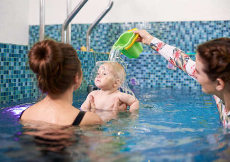 Image of swimming lesson for infants. Young mother holding her little baby, coach pouring out some water on babys head. Concept of early development and care