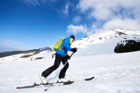 Photo for Happy tourist in colorful clothing and sunglasses with backpack climbing on skis in deep snow on background of bright blue sky and beautiful mountain. Winter vacations, active lifestyle concept. - Royalty Free Image