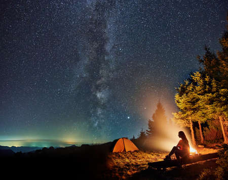 Photo pour Silhouette of young woman sitting and resting near tent and campfire in the mountains. Concept of relaxation under starry sky with Milky way. - image libre de droit