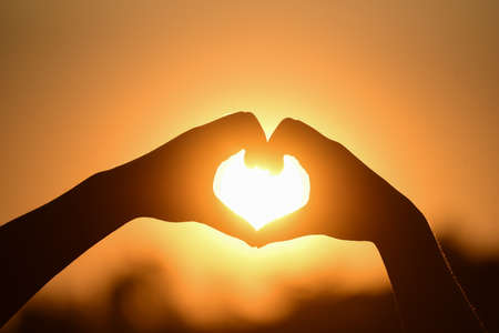 Photo for Silhouette hand made heart shape on the sunset background. Send love for the person you love Concept. - Royalty Free Image