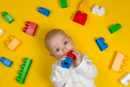 Baby playing with colorful blocks on yellow background