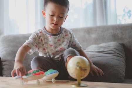 Foto de portrait of little funny boy ,toy model plane. Showing place on the globe, map. Concept travel, education. - Imagen libre de derechos