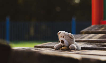 Lost teddy bear lying on wooden bridge at playground in gloomy day, Lonely and sad face brown bear doll lied down alone in the park, lost toy or Loneliness concept, International missing Children day