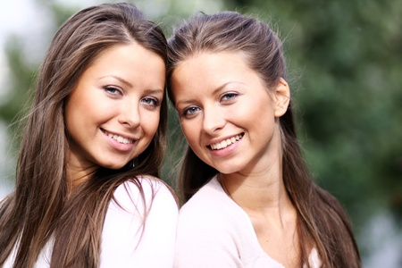 Twins of sister - women in summer park