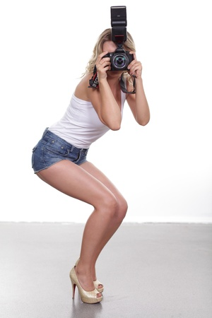 Cheerful woman shooting with a camera against white background