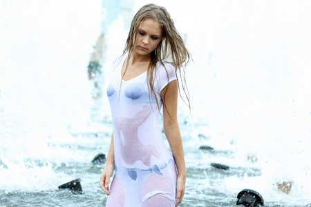 Young sexy woman bathes in a city fountain