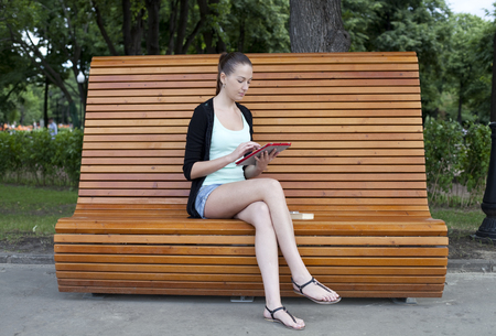 Young woman using a tablet computer on a park bench