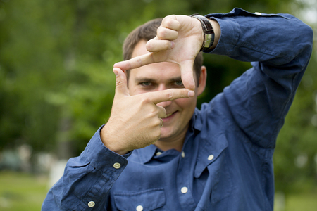 Photo for Focus on hand. A man looking and focusing through his hands, on green summer background - Royalty Free Image