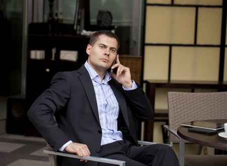 Young businessman talking on a cell phone while sitting in a summer cafe