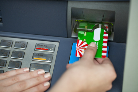 Female arms Take cash from the ATM, close up