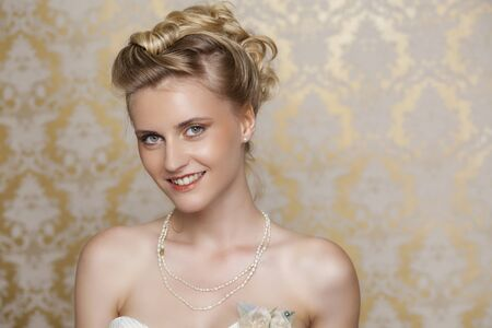 Attractive young blonde bride with beautiful wedding hairstyle