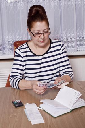 Elderly woman holding money in hand