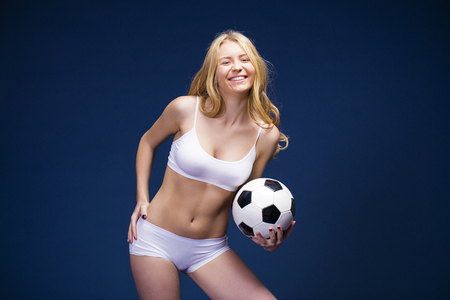 Photo for Happy girl holding a soccer ball. Young beautiful blonde woman in white fitness clothing, dark blue isolated background - Royalty Free Image