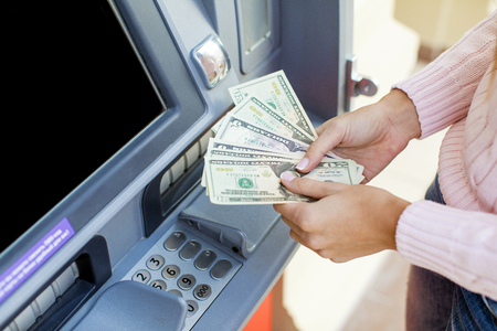Photo pour Repayment on credit. Woman hand withdrawing money from outdoor bank ATM - image libre de droit