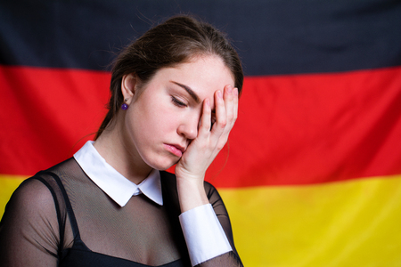 Portrait of a beautiful calm brunette girl in the background of the German flag