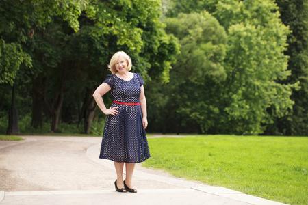 Foto für Happy elderly woman in blue dress on the background of summer park - Lizenzfreies Bild