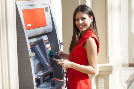 Foto de Young happy brunette woman in red dress withdrawing money from credit card at ATM - Imagen libre de derechos