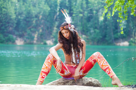 Foto per Portrait of a beautiful sexy young woman in Indian costume posing against a forest lake - Immagine Royalty Free