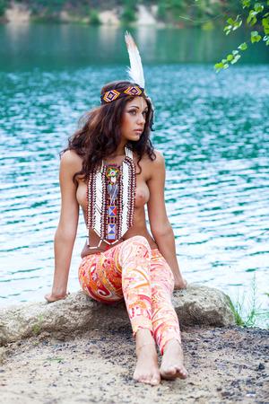 Foto de Portrait of a beautiful sexy young woman in Indian costume posing against a forest lake - Imagen libre de derechos