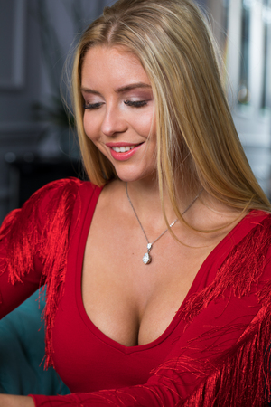 Foto de Beautiful young blonde girl in a red sexy dress sitting on a sofa in a beauty salon - Imagen libre de derechos