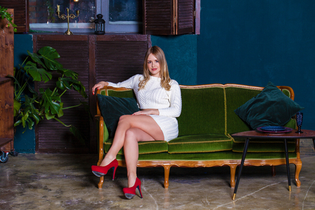 Photo pour Full length of a beautiful blonde sexy woman in white knitted dress sitting in green armchair in dark studio - image libre de droit