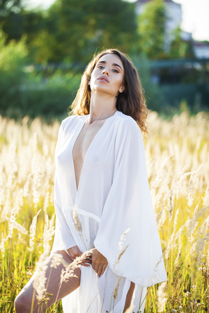 Portrait close up of young beautiful brunette woman in white dress, posing at sunset in the field