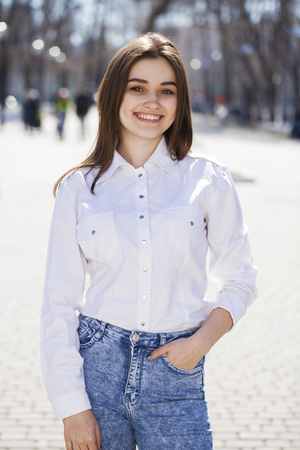 Photo pour Close up. Young beautiful brunette girl in white shirt posing on spring park - image libre de droit