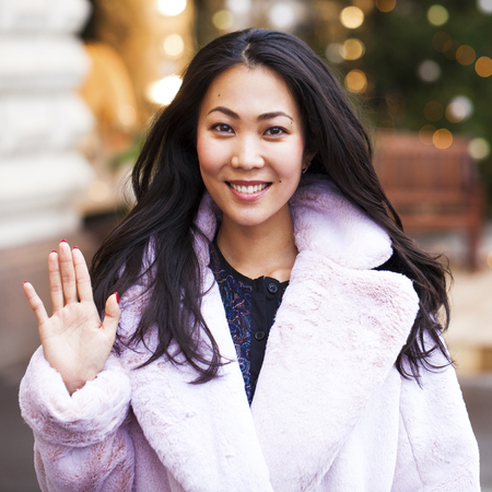 Photo pour Happy asian woman in winter coat from faux fur, walking on red square, Russia - image libre de droit