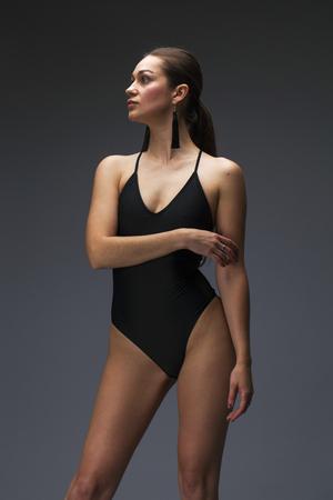 Photo pour Sexy fashion brunette woman in black bathing suit posing in the studio on a gray background - image libre de droit
