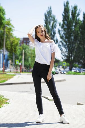 Photo for Full body young model. Portrait of young beautiful brunette woman in jeans and white blouse walking in summer street - Royalty Free Image