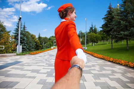 Photo pour Follow Me, Beautiful stewardess dressed in official red uniform of Airlines, Summer park outdoors - image libre de droit