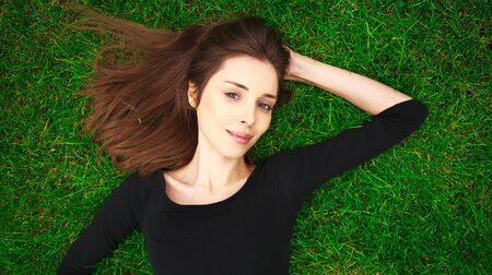 Photo for Top view portrait of a young beautiful woman in black dress lies on a green lawn in a park - Royalty Free Image