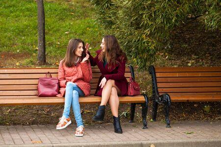 Photo pour Two beautiful young women resting on a bench in the autumn park - image libre de droit