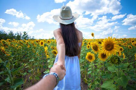 Photo pour Follow me, young girl holding a guy hand a field of sunflowers - image libre de droit