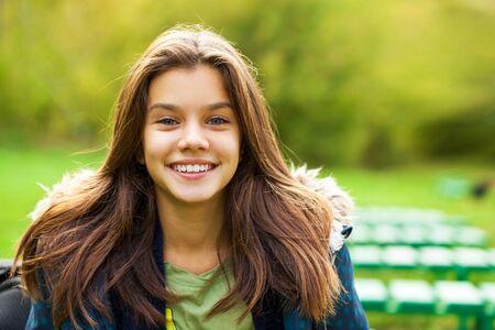 Photo pour Portrait of a young brunette girl in the background of a summer park - image libre de droit