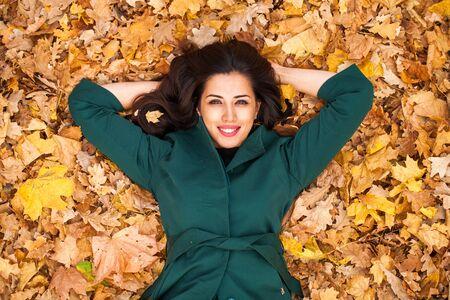 Photo pour Young brunette woman in green coat on background autumn park - image libre de droit
