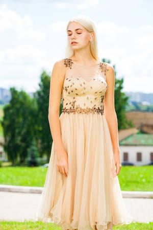 Photo pour Portrait of a young beautiful blonde woman in beige dress - image libre de droit