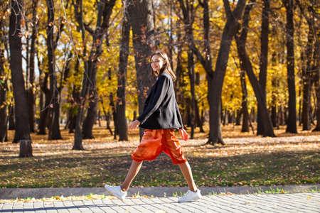 Foto de Full body portrait of a young brunette woman in orange skirt walking in autumn park - Imagen libre de derechos