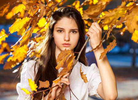 Photo pour Young beautiful girl in a purple sweater lies on fallen autumn leaves - image libre de droit