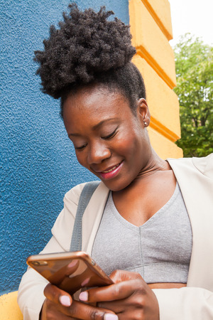 Medium shot of an african young woman in sportswear looking at His mobile phone with a colorful blue and yellow wall
