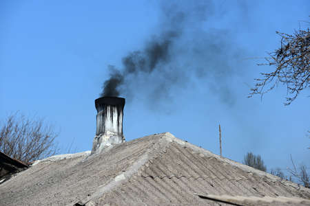 Photo pour A pipe with black smoke on the roof of a residential building - image libre de droit